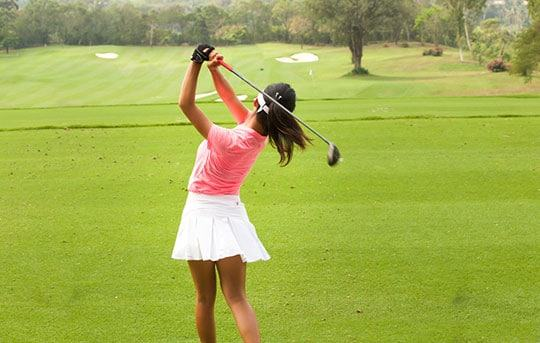 Female golfer swinging 12 degree driver