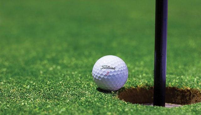 Golf ball near pin flagstick