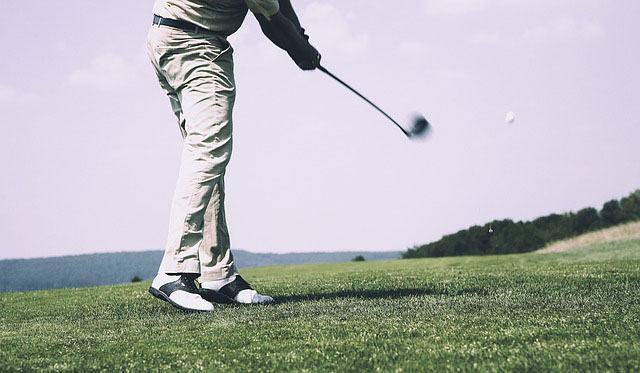 golfer swinging ping wedge