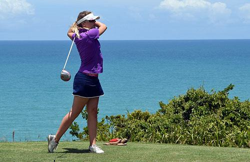 woman playing golf in blue skirt